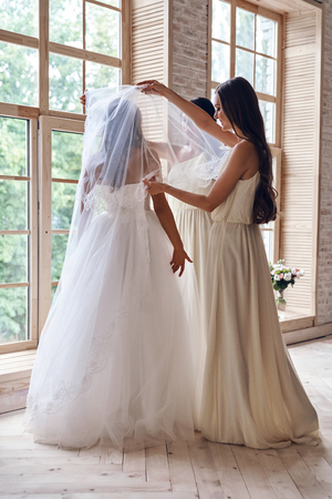Full length of bridesmaids helping bride to put on a veil while standing near the window together