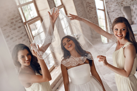 Top view of bridesmaids helping bride to put on a veil and smiling while standing in the fitting room