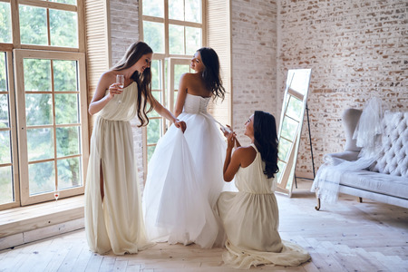 Gorgeous bride. Full length of two attractive young women adjusting a wedding dress on a beautiful bride Stock Photo