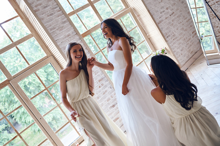 Bridesmaids helping bride with her wedding dress while standing in the fitting room