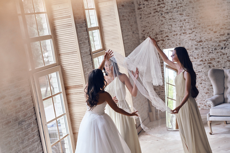 Her biggest day. Bridesmaids helping bride to put on a veil while standing near the window together