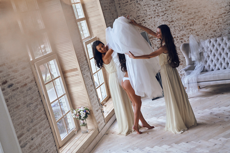 Full length top view of two attractive young women putting on a wedding dress on a bride while standing near the window together Stock Photo