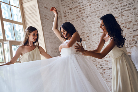 Preparation before wedding. Two attractive young women adjusting a wedding dress on a beautiful bride while standing near the window together