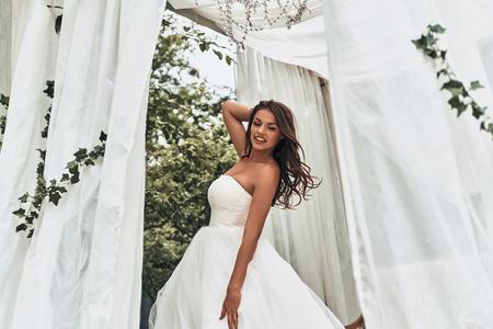 ウェディングドレスの魅力的な若い女性は、屋外に立っている間頭の後ろに手を維持し、笑顔 写真素材