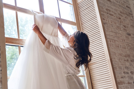 Making sure it is perfect. Beautiful young woman in silk bathrobe touching her wedding dress while standing near the window Stok Fotoğraf