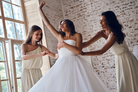 Making sure everything is perfect. Two attractive young women adjusting a wedding dress on a beautiful bride while standing near the window together