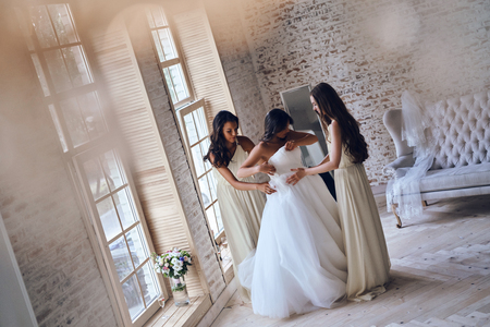 Important preparations. Full length top view of two attractive young women putting on a wedding dress on a bride while standing neat the window together