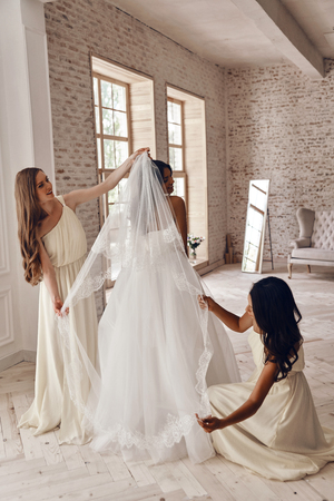 Helpful girlfriends. Full length of two charming bridesmaids helping bride to put on a veil while standing in the fitting room Stock Photo