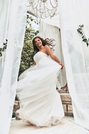 Full length of attractive young woman in wedding dress smiling and looking at camera while spinning around outdoors Stock Photo