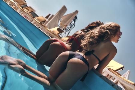 Besteden mooie zomerdag. Achtermening van twee mooie jonge vrouwen in bikini die terwijl in openlucht het in openlucht pool spreken