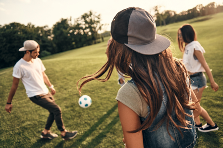 Just having fun. Group of young people in casual wear playing soccer while spending time outdoors
