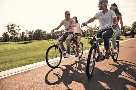 최고의 날. 야외에서 함께 자전거를 타는 동안 웃는 캐주얼의 행복 젊은 사람들 그룹