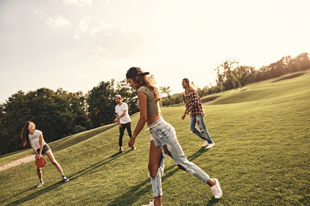 Summer activity. Group of young people in casual wear playing flying disk while spending carefree time outdoors