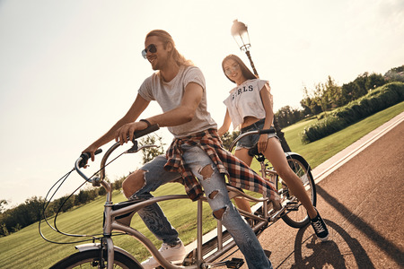 Love inspires them. Beautiful young couple in casual wear cycling together while spending carefree time outdoors