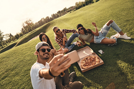 Creating happy memories. Group of young smiling people in casual wear taking selfie while enjoying food and drinks outdoors