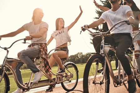 Life is awesome! Two young modern women giving each other high five while cycling with friends outdoors