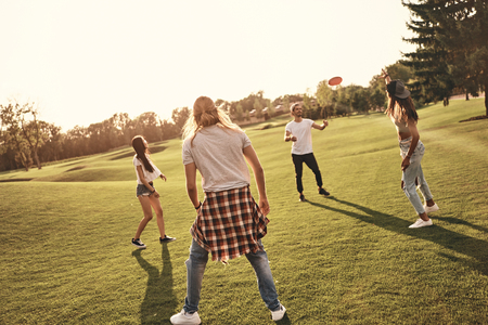 Having fun with friends. Full length of young people in casual wear playing flying disk  while spending carefree time outdoors