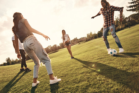 Amazing footwork. Full length of young smiling people in casual wear playing soccer while standing outdoors