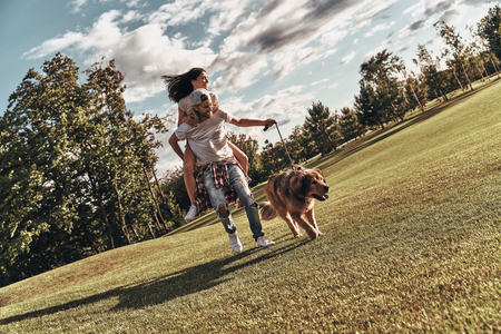 Following dreams together. Full length of handsome young man carrying young attractive woman on shoulders while walking with their dog outdoors