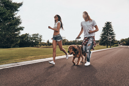 Great day together. Full length of beautiful young couple running with their dog while spending time outdoors