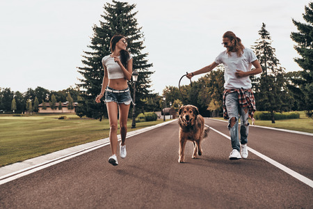 In one direction. Full length of beautiful young couple running with their dog while spending time outdoors