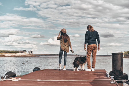 Enjoying great view. Full length rear view of beautiful young couple with dog standing on the wooden platform while spending time near the river Stock Photo