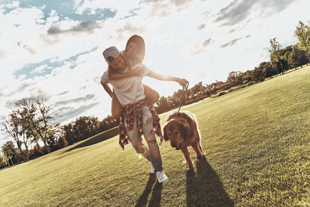 Simply happy. Full length of handsome young man carrying young attractive woman on shoulders while walking with their dog outdoors