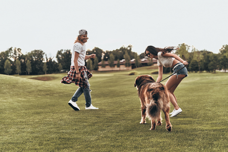Having so much fun.  Full length of beautiful young couple playing with their dog while spending time outdoors