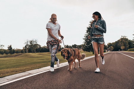 Who is going to come first? Full length of beautiful young couple running with their dog while spending time outdoors Stock Photo