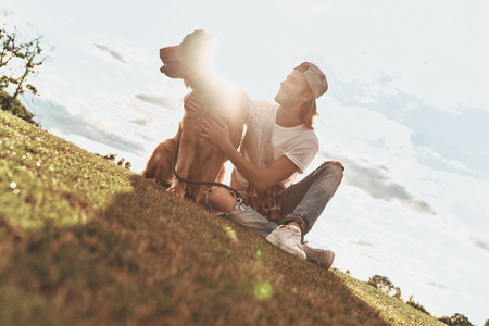 Real friend. Handsome young man and his dog sitting on the green lane while spending time outdoors