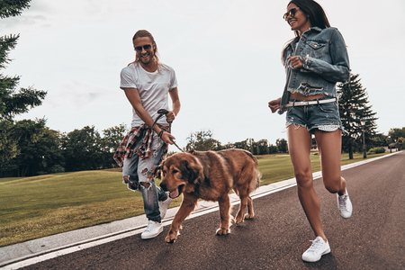 Young and full of energy. Full length of beautiful young couple running with their dog while spending time outdoors