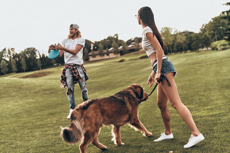 Dog keeps them active.  Full length of beautiful young couple throwing plastic disc while playing with their dog outdoors