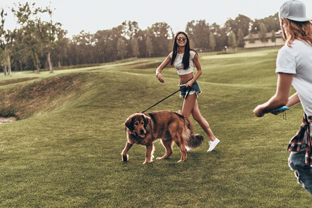 Carefree time together. Full length of beautiful young couple playing with their dog while spending time outdoors Stock Photo