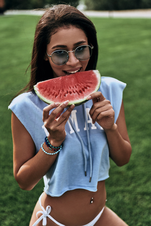 So delicious!  Attractive young woman in eyewear eating a slice of watermelon and smiling while sitting outdoors Фото со стока - 89017359