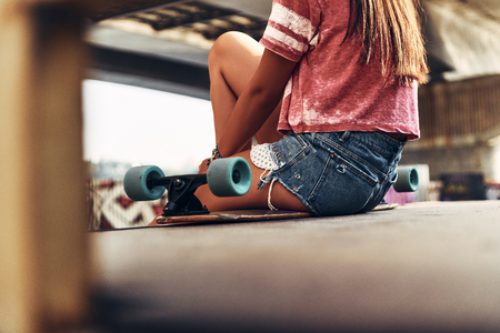Just relaxing. Close-up rear view of young woman sitting on the skateboard while spending time at the skate park outdoors