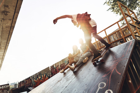 Born for boarding. Modern young men skateboarding while hanging out with his friends outdoors