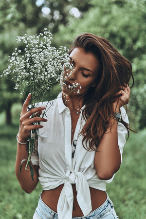 Enjoying springtime. Attractive young woman in casual wear holding flowers and keeping hand in hair while standing outdoors