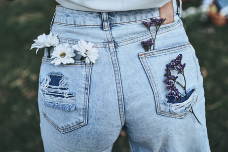 Spring style.  Close-up rear view of woman keeping chamomile and lavender in back pockets of her blue jeans while standing outdoors