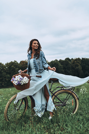 Looking for adventures. Full length of attractive young woman in dress smiling and looking away while standing next to her old fashioned bicycle on the meadow Banco de Imagens