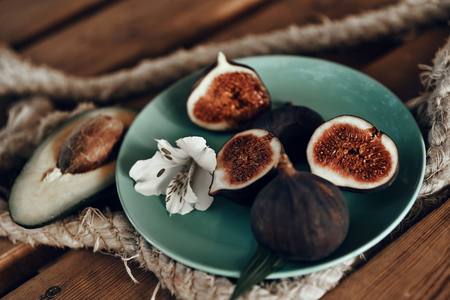 Organic fruits. Close-up shot of fig on a plate and avocado on the wooden table outdoors