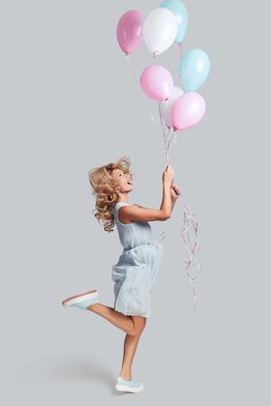 높은 비행 준비. 풍선을 들고 회색 배경에 점프하면서 웃는 쾌활 한 젊은 여자의 전체 길이 studio 쐈 어.