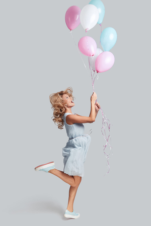 Ready to fly high. Full length studio shot of playful young woman holding balloons and smiling while jumping against grey background