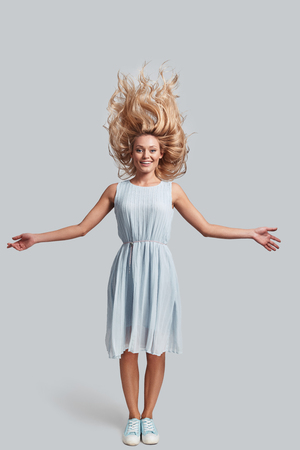 Hair like fire. Full length of attractive young woman with tousled hair looking at camera and smiling while standing against grey background Stock Photo