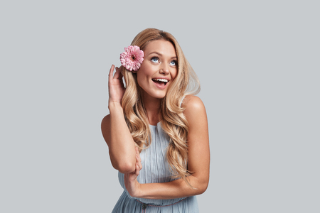 Fresh and cute. Attractive young woman with a flower in hair keeping arms crossed and smiling while standing against grey background Reklamní fotografie