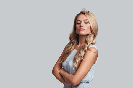 Real queen. Prideful young woman in crown keeping arms crossed while standing against grey background Stock Photo