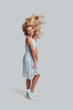 Strong and healthy hair. Full length of attractive young woman with tousled hair looking at camera and smiling while standing against grey background Stock Photo