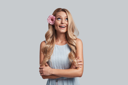 Cheerful beauty. Attractive young woman with a flower in hair keeping arms crossed and smiling while standing against grey background