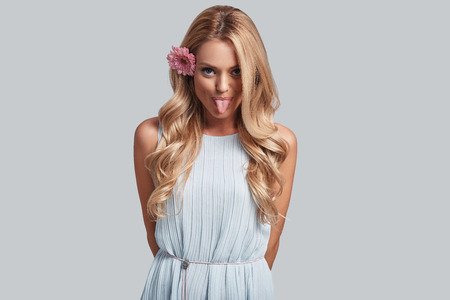 Bad girl. Playful young woman with a flower in hair looking at camera and sticking out tongue while standing against grey background