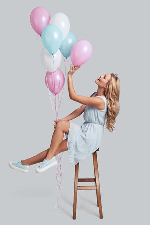 Fugir ... comprimento total, tiro do estúdio de mulher jovem e atraente na coroa segurando balões enquanto pairava no ar contra um fundo cinza