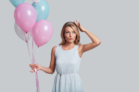 Checking the crown. Attractive young woman holding balloons and touching her head with hand while standing against grey background